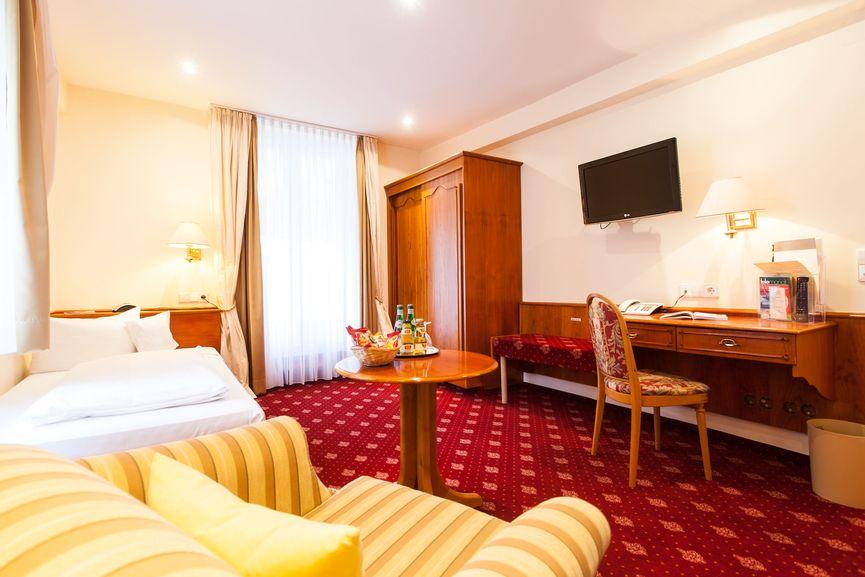 Schwarzwald Einzelzimmer mit Bett, Sessel, Schreibtisch und Schrank