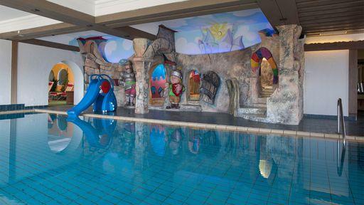 Entspannen Sie in unserem Hallen-Schwimmbad mit Panoramablick auf die Berge.
