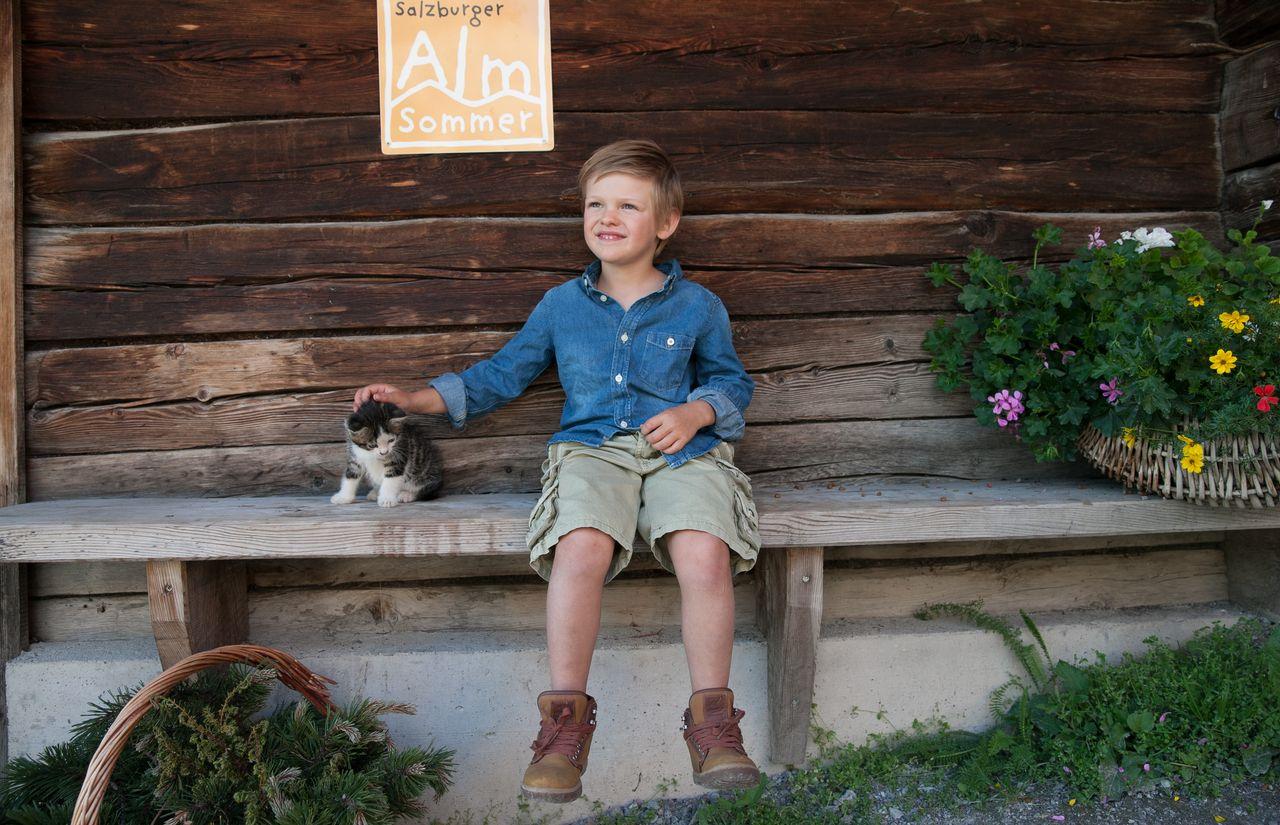 Bub mit Katze auf der Almhütte